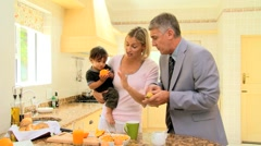Hurried man leaving wife and child in kitchen and going to work - stock footage