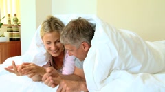 Young couple chatting and laughing under the duvet Stock Footage