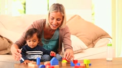 Stock Video Footage of Young woman showing her baby how to play with building blocks