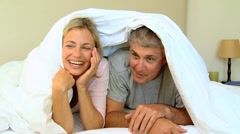 Young couple laughing and posing under the duvet Stock Footage
