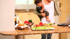 Mother holding baby and cooking etc - stock footage