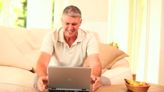 Middle-aged man overjoyed by what he sees on laptop Stock Footage