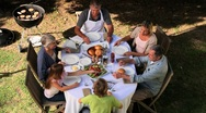 Family sorting out cutlery at garden table before eating Stock Footage
