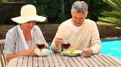 Mature couple laughing over lunch by swimming pool Stock Footage