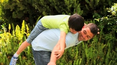 Father playing with son in garden Stock Footage