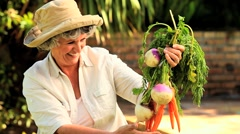 Mature woman admiring root vegetables - stock footage