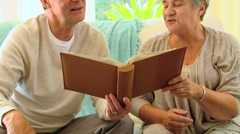 Retired couple looking at an album Stock Footage