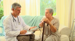 Doctor questioning patient while taking her blood pressure - stock footage