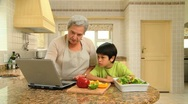 Woman cooking with her grandson Stock Footage