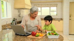 Woman showing her grandson how to cook - stock footage