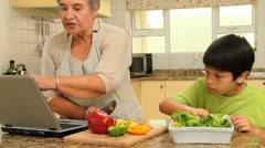 Little boy cooking with his grandmother Stock Footage
