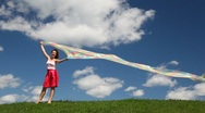 Woman stands with rainbow fabric on grass Stock Footage