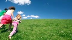 Happy family holding hands up hill - stock footage