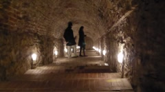 COUPLE IN LIT CAVE WALKWAY Stock Footage