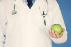 Male doctor holding green apple on blue background NTSC Stock Footage
