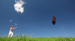 Boy plays kite in meadow against blue sky Stock Footage