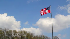 Flag with deep blue sky with white puffy clouds Stock Footage