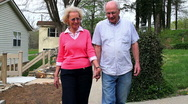 Retired couple holding hands walking towards camera Stock Footage