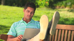 Relaxed man working on a laptop Stock Footage