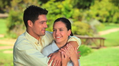 Cuddly couple sitting on a grass Stock Footage