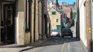 Stock Video Footage of View along a narrow street with golden stone buildings, pub on corner, car turns