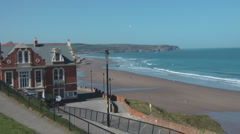 Path from cliff top to beach, passing red brick and sandstone Victorian hotel, Stock Footage