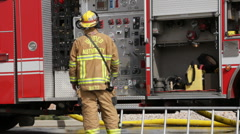 Firefighter looking at fire truck HD3933 Stock Footage