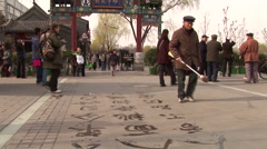 Old chinese calligrapher practicing in touristic Houhai lake district in Beijing Stock Footage