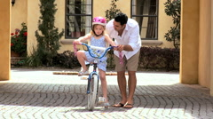 Ethnic Father Teaching Daughter on Bicycle - stock footage