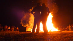 Couple Walk Up To Large Burning Fire Stock Footage