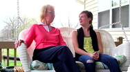 Grandma and grandaughter on porch swing talking. Stock Footage