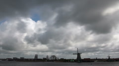 Clouds fly over Dutch landscape with windmills on rainy day Stock Footage
