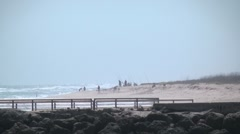 Beach scenic long shot people surf fishing far down the beach 1 h264 Stock Footage