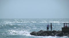 Beach scenic people fishing at end of pier on the rocks with waves crashing a Stock Footage