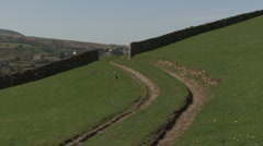 Track across hillside and gateway in dry stone wall near Reeth, Swaledale. Stock Footage