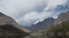 Time lapse of clouds moving over pristine lake and impressive Pakistan mountains Stock Footage