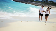 Attractive Couple Jogging Along Tropical Beach Stock Footage
