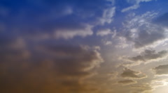 Time-lapse clouds in blue and orange sky. - stock footage