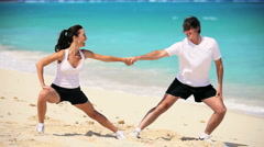 Healthy Couple Doing Muscle Stretches on Beach - stock footage