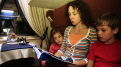 Mother reads book to son and daughter sitting in coupe riding train Stock Footage