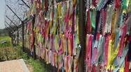 DMZ Panmunjon North Korean border ribbons attached to barber fences telephoto Stock Footage