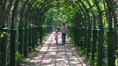 Mother and little daughter go through arched corridor braided plants Stock Footage
