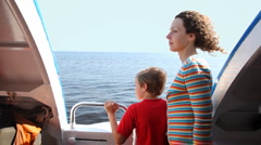 Mother and son stand at side of fast moving boat hydrofoil on sea Stock Footage