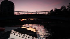 Boat floats under small bridge in St. Petersburg at night Stock Footage