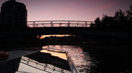 Stock Video Footage of Boat floats under small bridge in St. Petersburg at night