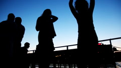 Silhouettes of two girls dancing on board ship sailing at night Stock Footage