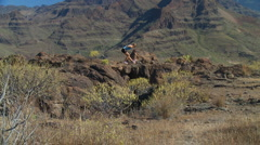 Crane shot of woman stretching in mountains Stock Footage