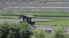 DMZ Panmunjon North Korean border rice fields and fisher boat on the river Stock Footage