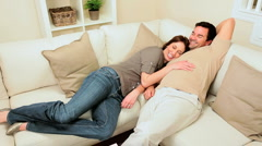 Young Couple Relaxing on Home Sofa Stock Footage