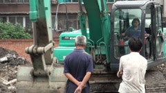 Two men watch an excavator take down a building in a Chinese city Stock Footage